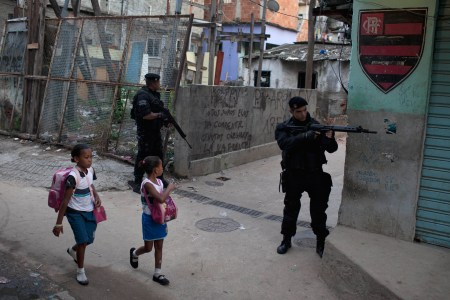 Students walk to school past military police officers patrollong in the Complexo do Alemao slum in Rio de Janeiro, Brazil, Tuesday March 27, 2012. Military police officers are replacing army soldiers patrolling the area at the slum complex. (AP Photo/Felipe Dana)