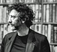 Neil Gaiman in front of a bookshelf.