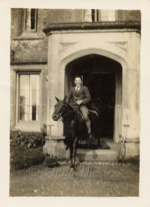 A man riding a horse out through the front door of a stately home.