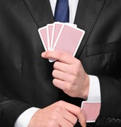 Person holding four cards in his hand and pulling one card from