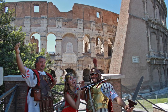Two costumed gladiators pose outside The Coliseum with travel blogger Amanda as part of a scam for money.