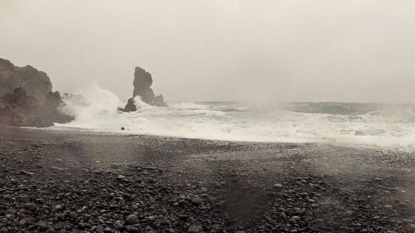Wave crashing against lava rocks on Djupalon beach