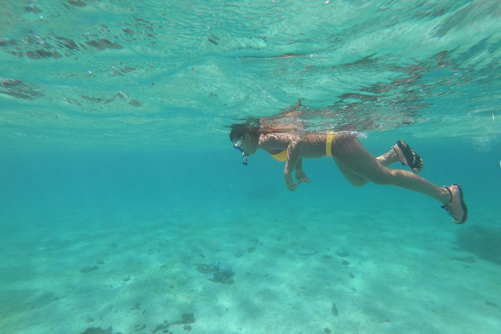 travel blogger Amanda snorkeling in Moorea. One of the best things to do in Moorea is snorkel. Add snorkeling to your Moorea itinerary.