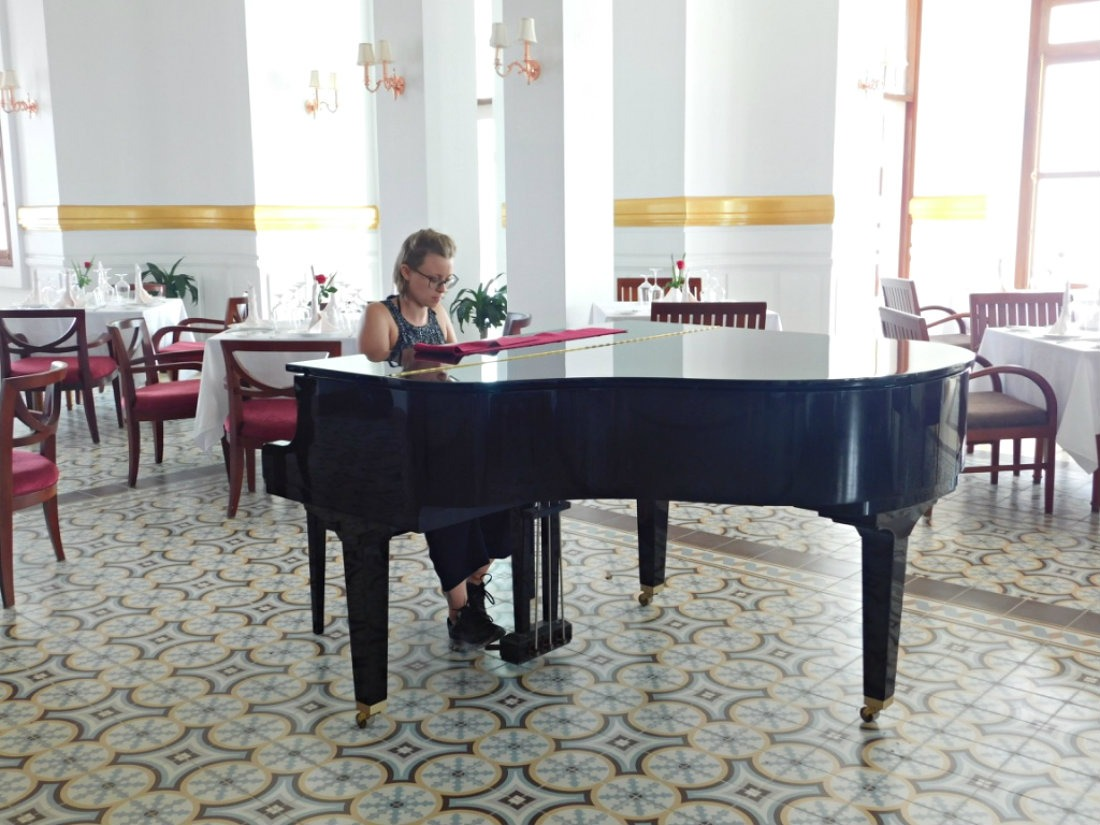 Playing piano at the Bokor Palace Hotel - one of the best things to do in Kampot
