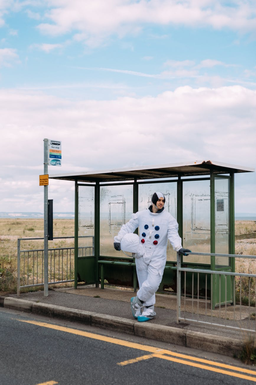 astronaut waiting at a bus stop