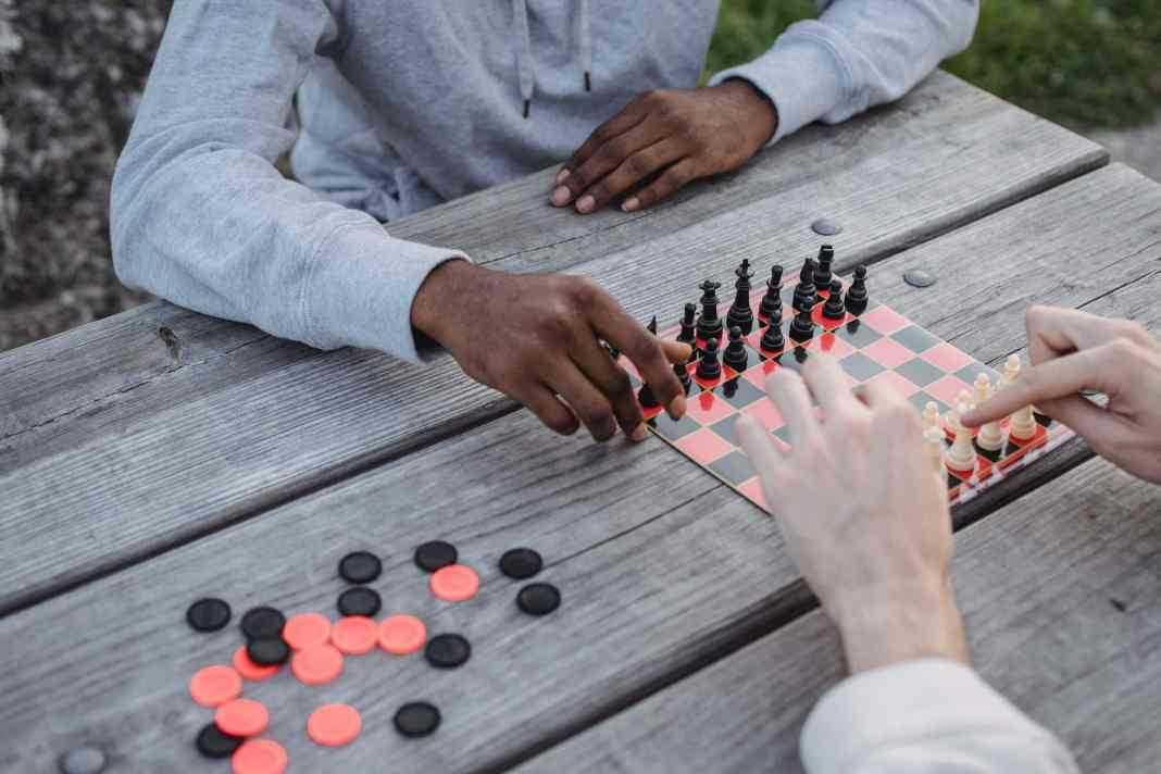 anonymous diverse men playing chess game in park