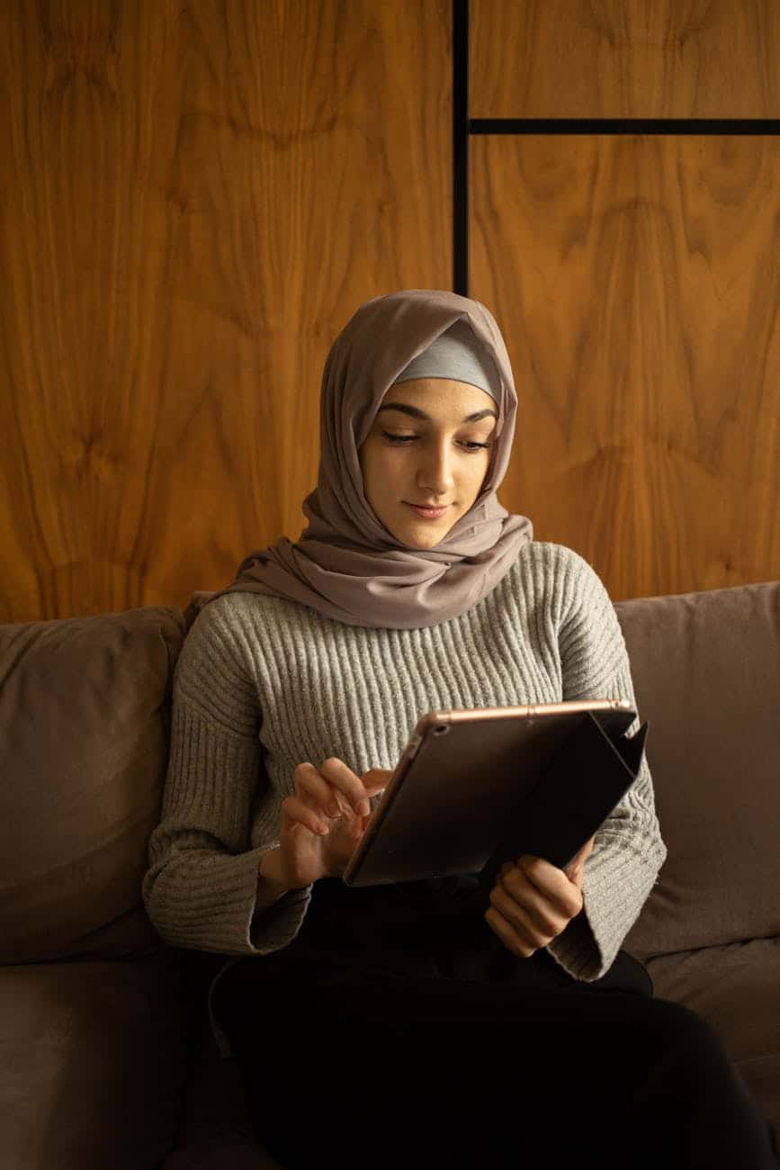positive muslim woman using tablet on sofa