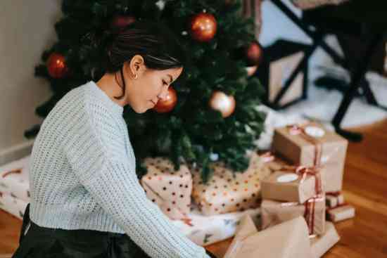 ethnic woman with pile of present boxes against christmas tree