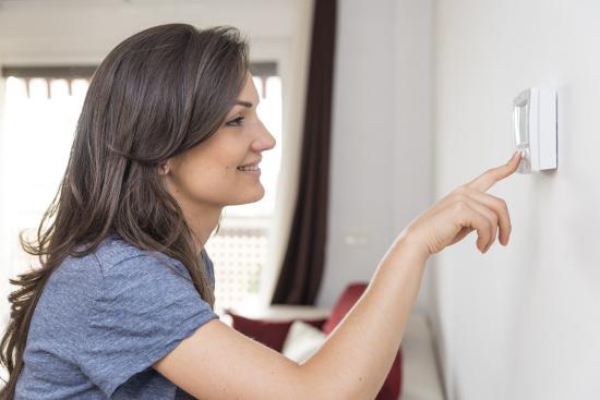Woman adjusting thermostat © santypan | dollarphotoclub.com