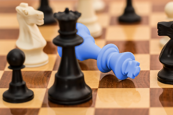 Chess game with blue king toppled in defeat.