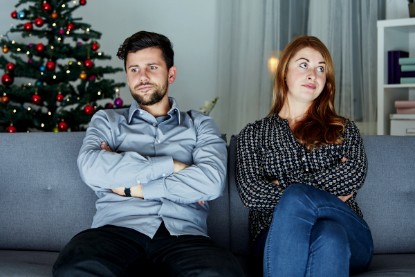 Unhappy couple on couch with Christmas tree in background