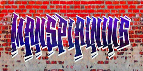 "Graffiti on brick wall reading ""mansplaining"""