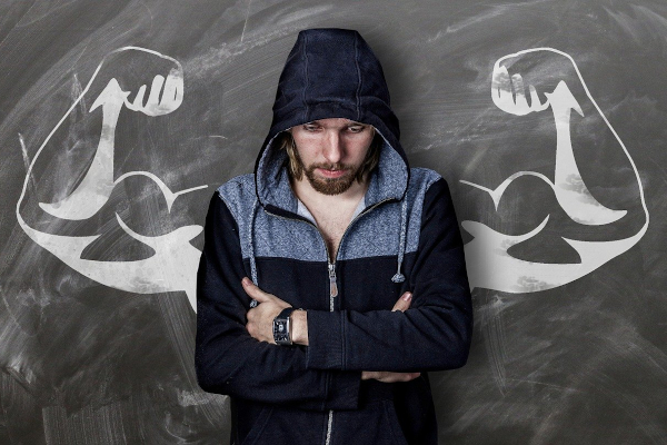 Sad man standing in front of drawing of arms with big biceps.