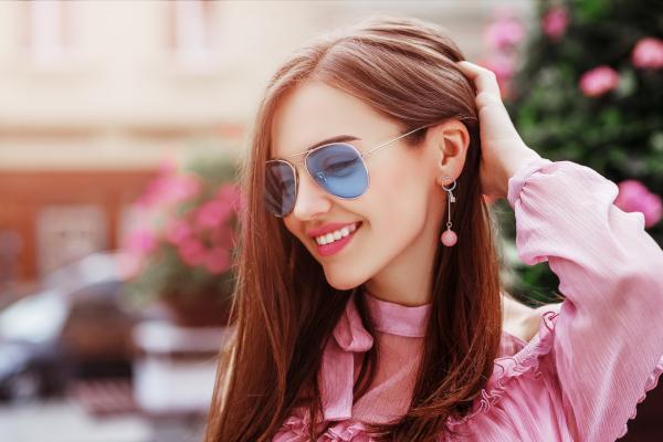 Smiling woman wearing blue sunglasses.
