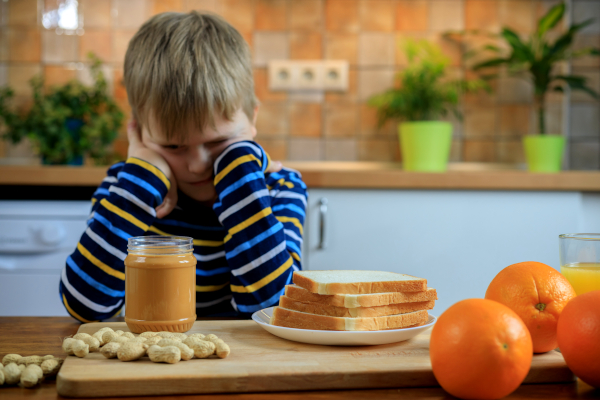 Boy looking at bread and peanut butter.