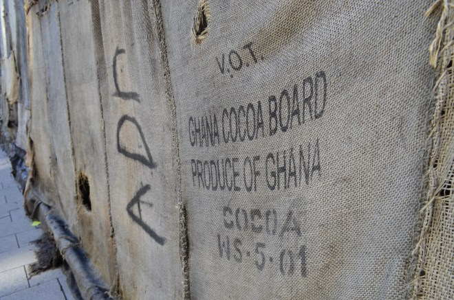 Close-up of the veiled gate guard at documenta 14 in Kassel in 2017, installation by Ibrahim Mahama. The jute bags were used to transport cocoa, coffee, rice, beans and charcoal from Ghana to Europe and the USA. Thus, the installation stands for world trade grown out of colonial structures. Source: Tanja Verena Matheis