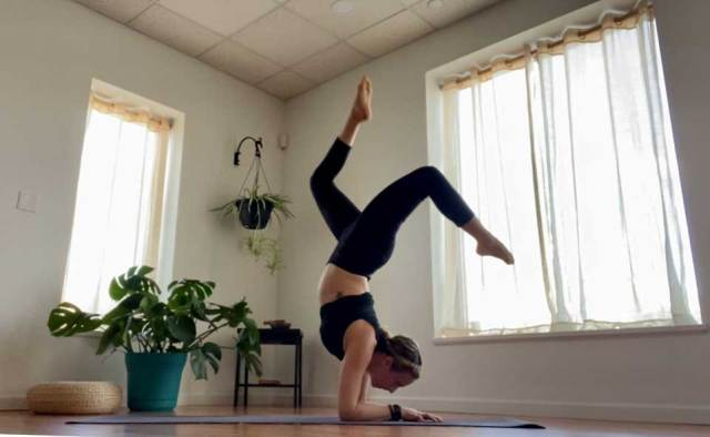 A yoga teacher in an inverted handstand pose