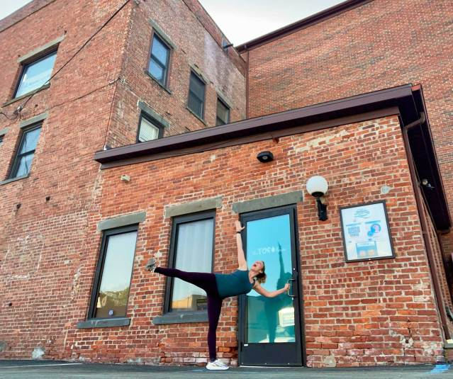 A yoga teacher outside a brick studio poses without a mask