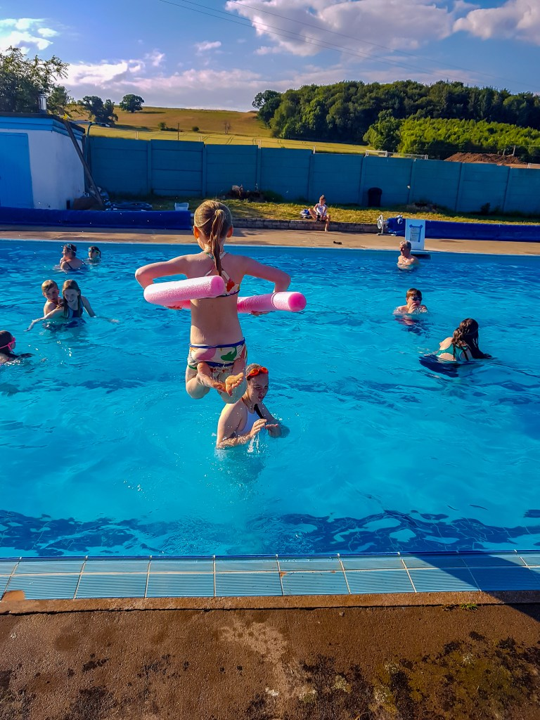 jumping into Helmsley open air swimming pool