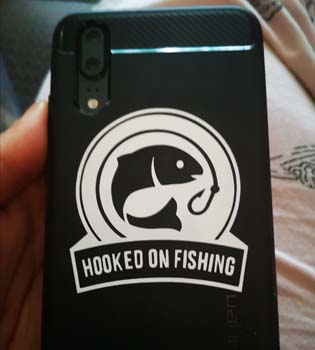 Black spiegan mobile phone case with personalised white vinyl of hooked on fishing with image of a fish and a hook