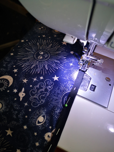 Sewing black bias binding to right side of celestial fabric