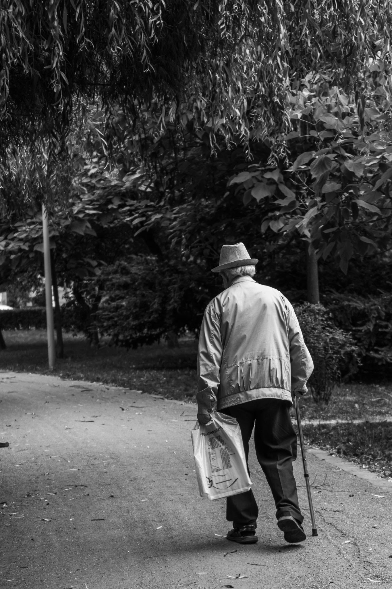 senior walking down dirt path with cane holding a bag