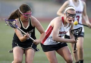 Southbury, CT- 07 May 2015-050715CM11- Pomperaug's Hayley McCormick, right, keeps her eye on the ball as Joel Barlow's Catarina Goncalves defends during their SWC lacrosse matchup in Southbury on Thursday. Christopher Massa Republican-American