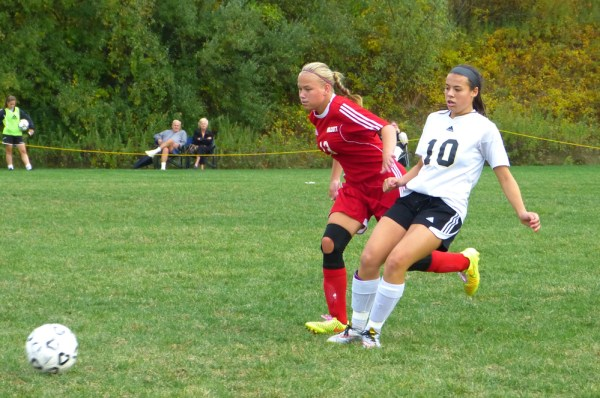 Wolcott's Tiona Watts, left, and Woodland's Sam Plasky chase down a loose ball during NVL soccer action Tuesday. The Eagles and Hawks played a scoreless draw. (Palladino/RA)