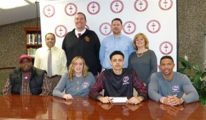 Sacred Heart's Tyrn Flowers signed his letter of intent Wednesday to attend the University of Massachusetts on a basketball scholarship. Seated from the left are his father, Bryan Flowers, mother Dawn Corcoran, Flowers, and brother Bryant Corcoran. Standing from the left are principal Anthony Azzara, athletic director Michael Madden, head basketball coach Jon Carroll, and school president Eileen Regan. (Palladino/RA)