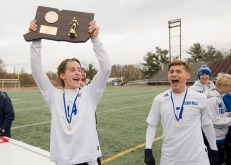 John Mudgett (14) heists the championship plaque in front of teammate Nick Lutrzykowski (7) following their 3-2 win over Suffield to capture the Class M state title Saturday at Willow Brook Park in New Britain. Jim Shannon Republican-American