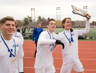 Lewis Mills' Nick Lutrzykowski (7), Peter Christiano (10) and John Mudgett (14) walk around with their state champion plaque following their 3-2 win over Suffield in Class M state finals Saturday at Willow Brook Park in New Britain. Jim Shannon Republican-American
