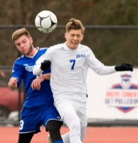 Lewis Mills' Nick Lutrzykowski (7) heads the ball in front of Suffield's Alek Cotnoir (3) during their Class M state final game Saturday at Willow Brook Park in New Britain. Jim Shannon Republican-American