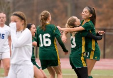 Holy Cross' Alyssa Hebb (16) and Erin Goggin (3) congratulate Adalisse Padilla (10) after she scored on a penalty kick during their Class S state final game against Old Lyme Saturday at Middletown High School. Jim Shannon Republican-American