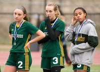 Holy Cross' McKenna Ellsworth (2), Erin Goggin (3) and Jasmine Thorpe (5), look on as Old Lyme receives their championship medals following their Class S state final game Saturday at Middletown High School. Jim Shannon Republican-American