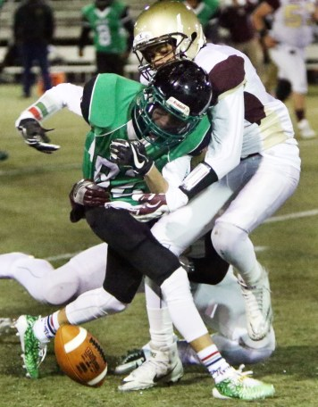 #82 Alemar Blondet of Wilby High fumbles as #1Juan Salazar of Sacred Heart/Kaynor defends in the 1st quarter at Municipal Stadium in Waterbury Wednesday.Steven Valenti Republican-American