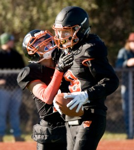 Watertown's Thomas Hassan (8) is congratulated by teammate Daniel Graziano (17) after scoring a touchdown during their Thanksgiving Day game Thursday at Watertown High School. Jim Shannon Republican-American