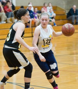 Wolcott Tech's Katie Benedict (21) drives to the basket past Kaynor Tech's Maggie DeSantis (13) during their game Thursday at Wolcott Tech school in Torrington. Jim Shannon Republican-American
