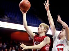 #12 Garrett Sattazahn of Wamogo puts up a shot over #12 Nick Wright of Cromwell during the CIAC Division V Finals at Mohegan Sun Arena in Uncasville Saturday. Wamogo lost 58-40. Steven Valenti Republican-American