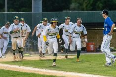 WATERBURY, CT. 25 May 2018-052518BS964 - Holy Cross players led by John Greene (5), center, and Brian Parzyek (33), right, storm the field towards first base as St Paul Pitcher Walker Sharp walks off the mound after waking in the winning run for Holy Cross during the NVL Championship game between St Paul Catholic and Holy Cross at Municipal Stadium on Friday evening. Holy Cross won 6-5. Bill Shettle Republican-American