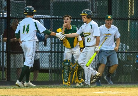 Holy Cross's Austin Brown celebrates with teammate Connor Goggin (14) and Holy Cross catcher John Greene (5), after crossing the plate for the tying run during the NVL Championship game between St Paul Catholic and Holy Cross at Municipal Stadium on Friday afternoon. Holy Cross came back to win 6-5. Bill Shettle Republican-American