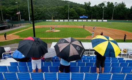 Fans use umbrellas to protect themselves from the occasional rain showers that popped up all day Wednesday during the Mickey Mantle World Series game game between South Troy (NY) and Foutch of Flint Township (MI) Wednesday at Municipal Stadium in Waterbury. Jim Shannon Republican American