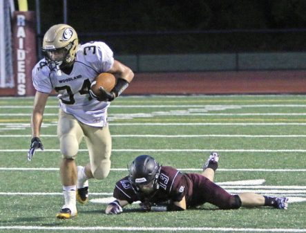 Woodland's Edit Krivca (34) breaks a tackle from Torrington's Michael Brown (13) during NVL action at Torrington High School Friday night. Woodland defeated Torrington Michael Kabelka / Republican-American