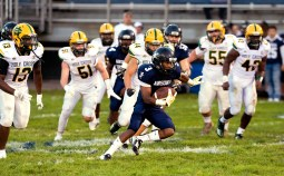 Ansonia's Shaykeem Harmon (3) runs past a group of Holy Cross defenders for a big gain during their game Friday at Nolan Field in Ansonia. Jim Shannon Republican American