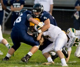 Holy Cross' Corey Fappiano (4) gets sacked by a pair of Ansonia defenders during their game Friday at Nolan Field in Ansonia. Jim Shannon Republican American