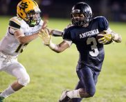 Ansonia's Shaykeem Harmon (3) gets pushed out of bounds by Holy Cross' Vin Graziano (15) during their game Friday at Nolan Field in Ansonia. Jim Shannon Republican American