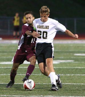 Naugatuck High School's Bruno Silva battles Woodland High School's Sean Swanson for the ball during the boys varsity soccer game in Naugatuck on Thursday. Emily J. Reynolds. Republican-American
