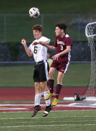 Naugatuck High School's Freddie Longo and Woodland High School's Ryan Swanson each try to head the ball over the other during the boys varsity soccer game in Naugatuck on Thursday. Emily J. Reynolds. Republican-American