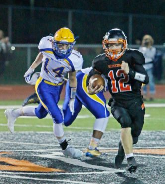 Watertown's Xavier Powell (#12) rushes for yardage against Seymour's Jacob Carb (#14) during NVL action Friday at Watertown High School. Michael Kabelka / Republican-American