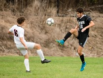 Kaynor Tech's Erick Silva (12) chips the ball over Goodwin Tech's Tristan Pelletier (16) during their game Monday at Kaynor Tech High School in Waterbury. Jim Shannon Republican American