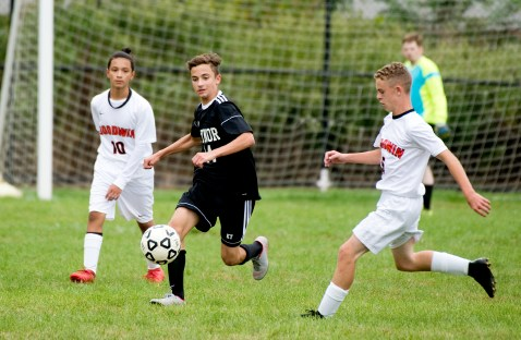 Kaynor Tech's Simon Carvalho (14) runs down the ball from Goodwin Tech's Robert LaBlond (5) during their game Monday at Kaynor Tech High School in Waterbury. Jim Shannon Republican American